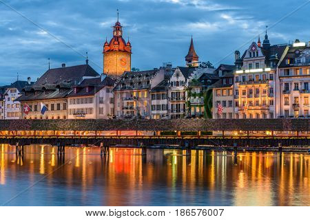 Night view towards Chapel Bridge (Kapellbruecke) together with the octagonal tall tower (Wasserturm) it is one of the Lucerne's most famous tourists attraction