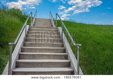 A large flight of steps climb this grassy hill with bright blue sky.