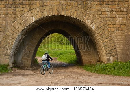 A man on a bicycle rides in a tunnel under a railway. The old tunnel is made of stone.