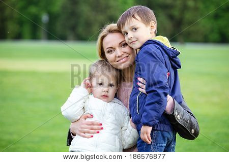Happy young woman hugging sons in park