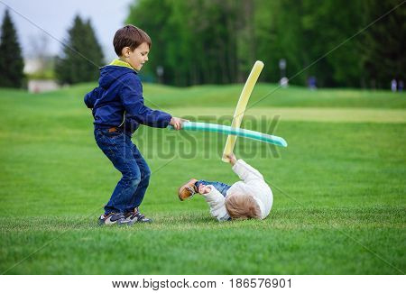 Preschool boys fighting with toy swords in park