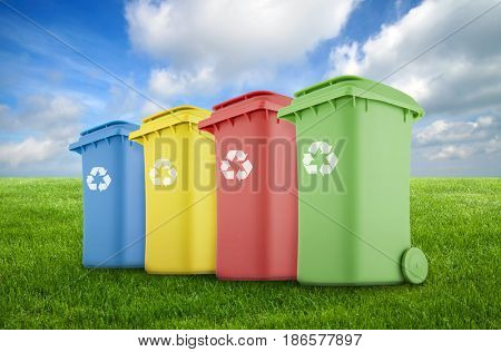 Four colorful recycle bins on green grass.
