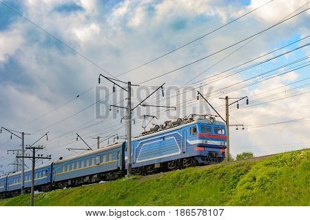 Passenger Train Rides On An Electrified Line Against A Blue Sky