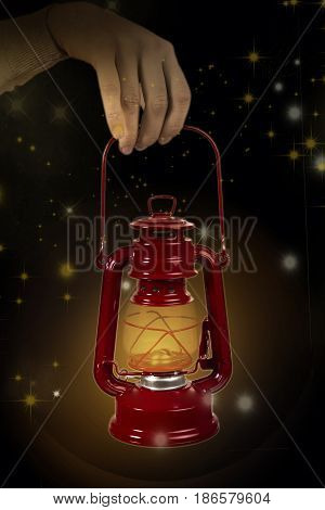Old lamp with light in hand on a starry background