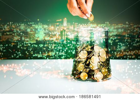 double exposure of hand drops money into a glass bottle with cityscape background savings concept