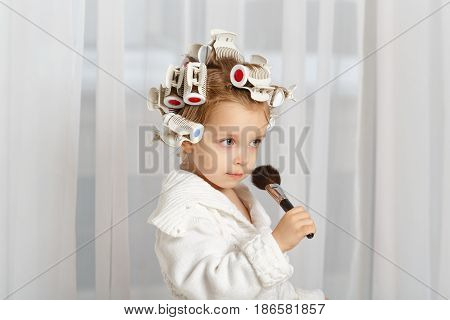 Little girl fashionista. A girl in a curler and a robe is holding a makeup brush. Little coquette posing. Human emotions. She does make-up.
