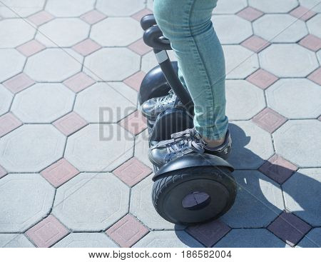 woman legs dressed in green jeans and sneakers ride gyroscooter or hoverboard
