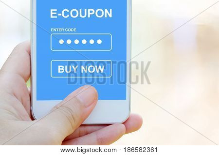 Hand holding smart phone with discount coupon code on screen over blur store background on line shopping business E-commerce technology and digital marketing background