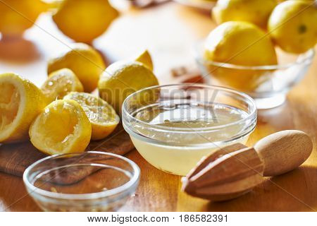 kitchen table with bowl full of lemon juice freshly squeezed with wooden reamer