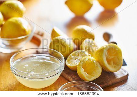 bowl of lemon juice and pile of freshly squeezed lemons