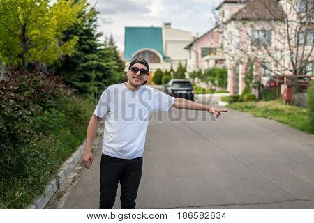 Young hipster man in sunglasses hitching on road. Summer time