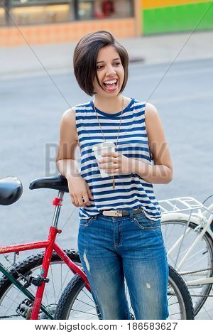 Portrait of beautiful smiling laughing young hipster latin colombian girl woman with short hair bob in blue ripped jeans striped tshirt holding cup of coffee leaning on bike in city