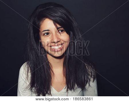 Portrait of beautiful smiling Hispanic latino girl woman with dark brown eyes long dark messy untidy hair in white shirt posing in studio on dark black background looking away
