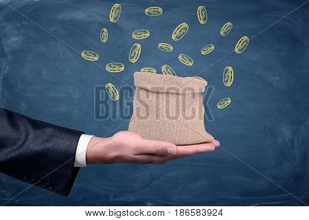 A businessman's hand turned up and a small money bag standing on it with drawn coins on blue background. Getting wealthy. Rags to riches. Accessible business start.