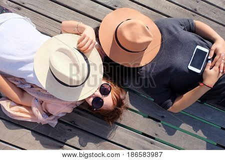 Two women relaxed and hat. Lie on a wooden bridge that extends to the sea. Relax concept.