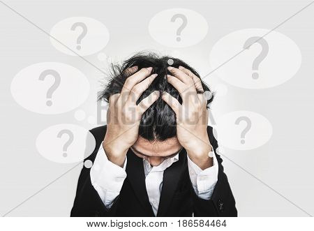Businessman touching his head, with question marks sign on speech bubbles