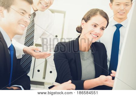 Mixed race business colleagues looking at computer screen discussing work
