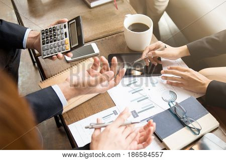 Business people calculating and discussing financial documents in cafe