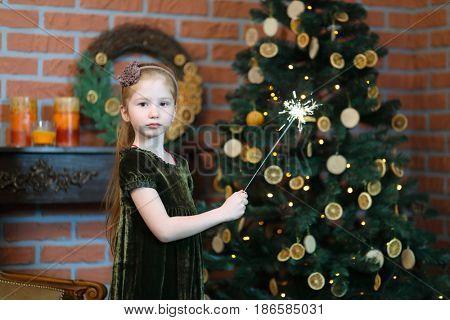 Little girl in dress holds sparkler near beautiful christmas tree in room