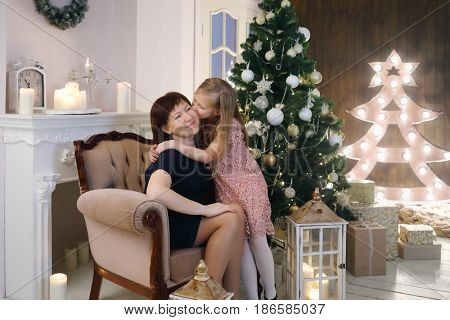 Woman sits in armchair and daughter kisses she in room with christmas tree and lanterns on floor