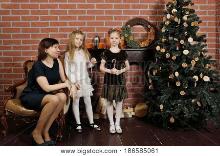 Woman with two daughters pose near christmas tree in stylish studio