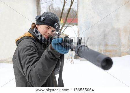 Teenager with gun takes aim during lasertag game outdoor at winter day