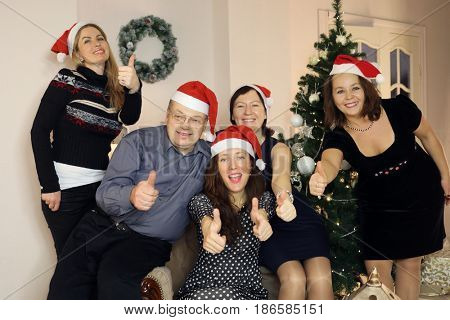 Five people in santa caps thumb up near near christmas tree, focus on man and woman in middle