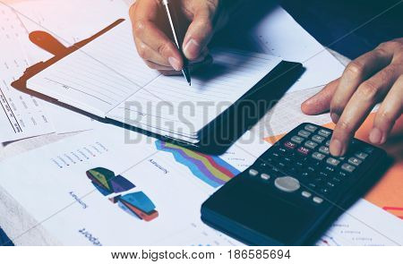 Woman Writing Make Note And Calculate Finance On Desk With Analyaing Summary Report At Home Office.