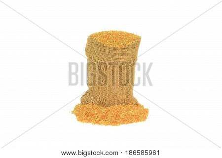 Raw uncooked Tri-colored (Tricolor) (Tri color) cous-cous (couscous) colured with tomato and spinach powder in burlap bag (sack) and spilled on pile over white background - isolated