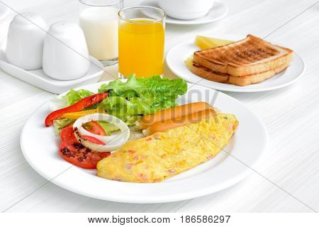 Breakfast including omelet sausagemilkjuice toast and colorful salad with Italian dressing