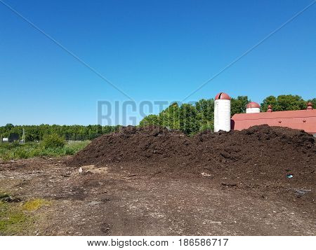 large pile of mulch and dirt and farm house