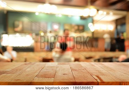 Wood table top on blur background of coffee shop interior with some people - can be used for display or montage your products