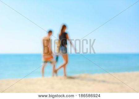 Blur image of couple walking at the beach summer holiday background concept