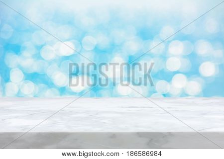 White marble stone countertop on light blue bokeh abstract background - can be used for display or montage your products