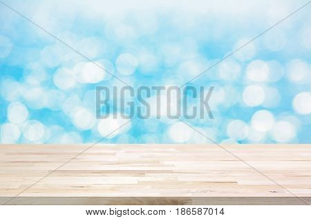 Wood table top on white blue bokeh abstract background - can be used for display or montage your products
