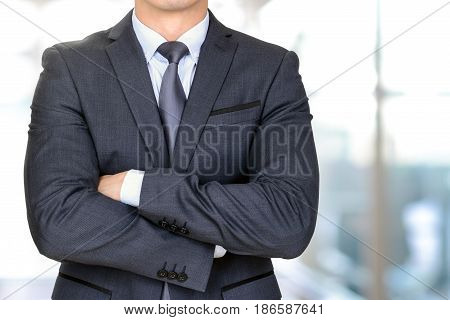 Anonymous businessman in dark gray suit crossing his arms on blur office hallway background