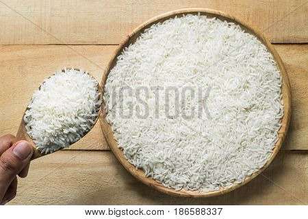 Close up jasmine rice in wooden spoon. top view