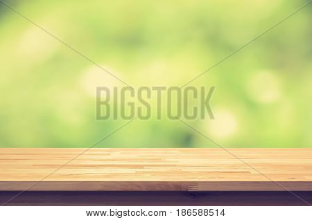 Wood table top on green bokeh abstract background vintage tone - can be used for display or montage your products