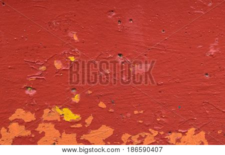 Texture of the concrete surface painted with red paint and irradiated below with spots of orange and yellow