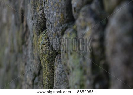 background old stonework slightly greenish in places disappearing in perspective to the left with a focus on the foreground