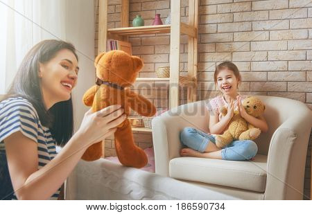 Happy loving family. Mother and her daughter in kids room. Funny mom and lovely child having fun and playing performance in the puppet theater indoors. Teddy bear.