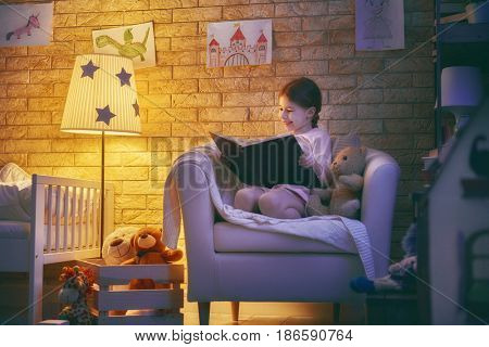 Cute little child girl reading a book under a lamp. Kid girl sitting in armchair.