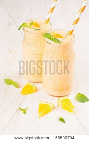 Freshly blended orange citrus smoothie in glass jars with straw mint leaf close up. White wooden board background.
