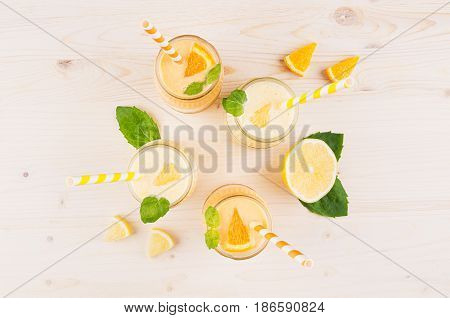 Freshly blended orange and yellow lemon smoothie in glass jars with straw mint leaf top view close up. White wooden board background.