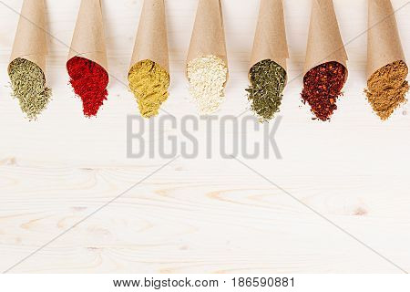 Assortment of different colorful powder seasoning close-up in paper corners on white wooden board with copy space.