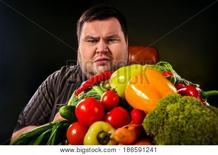 Diet fat man eating healthy food with vegetables cauliflower and sweet pepper with radish, tomatoes for overweight person. Fat man with a hill of fresh vegetables.