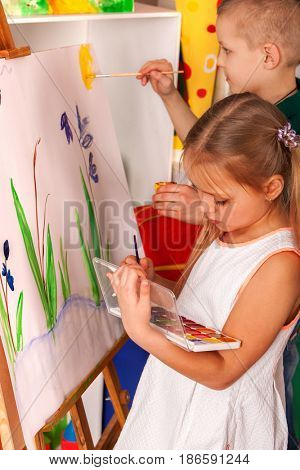 Children painting on easel. Girl with boy learn paint in class school. Child picture on background.