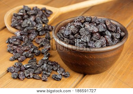 Raisins in bowl with wooden spoon on wooden background