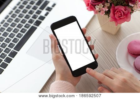 Women hands holding phone with isolated screen near laptop in cafe