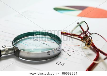 Business summary reports and a magnifying glass with glasses on table office. Concept of Data Analysis Investment Planning Business Analytics.